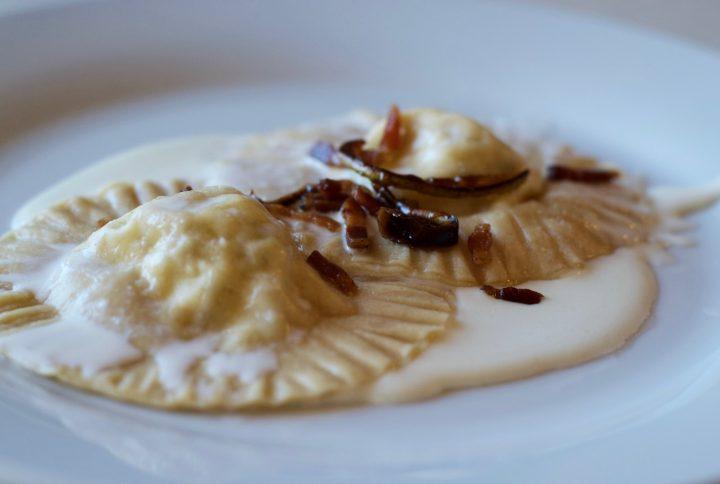 Cappellacci con pere caramellate e pancetta croccante su fonduta di pecorino